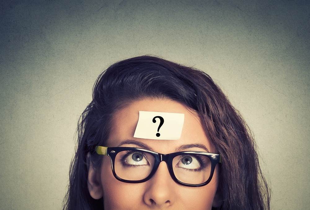 thinking woman with question mark on gray wall background.jpeg